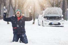 Gefrustreerde bestuurder naast gebroken auto De reisproblemen van de wintertijdweg en hulpconcept royalty-vrije stock fotografie