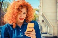 Gefrustreerde boze vrouw die met rood krullend haar aan mobiele telefoon kijken royalty-vrije stock foto's