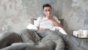 Gefrustreerde gebaarde heer met afvegende neus op hoge temperatuur in bed stock footage