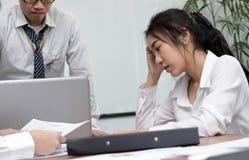 Gefrustreerde gedeprimeerde jonge Aziatische bedrijfsvrouw met handen op gezicht die aan streng probleem tussen vergadering in bu royalty-vrije stock afbeelding