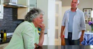 Gefrustreerde hogere man die op vrouw in keuken 4k schreeuwen stock videobeelden