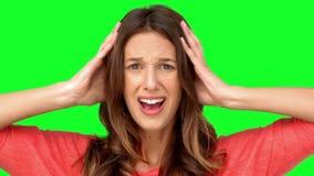 Gefrustreerde vrouw die haar hoofd tussen handen houden stock footage