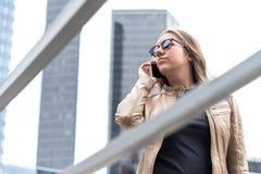Gefrustreerde vrouw die op de telefoon in de stad spreken stock fotografie