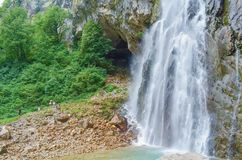 Gega waterfall in the mountains of Abkhazia. A group of people next to that. royalty free stock image