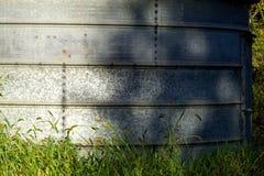Gegalvaniseerde bakkant met schaduwen die in het groene gras tonen royalty-vrije stock foto's