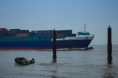 Gegenüberliegend: großes conatiner Schiff, kleines Motorschiff mit Fischermann stockfotos