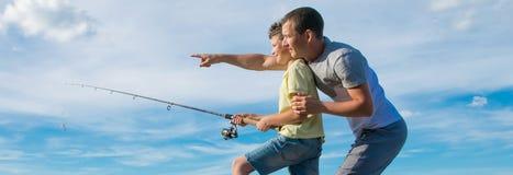 Gegen den blauen Himmel hält der Sohn eine Angelrute, und der Vater zeigt im Abstand stockbilder