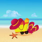 Gegenstände stellten mit Strandtasche, Pantoffeln, Sonnenhut und Sonnenbrille auf tropischem Strand ein Blaues Meer, Himmel u Lizenzfreies Stockfoto