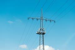 Gegenwärtiger Mast des elektrischen Turms mit telecomunication antennaa Stockfotografie