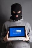 Gegevens stealing concept - gemaskeerde mens met computer over grijs Royalty-vrije Stock Afbeeldingen