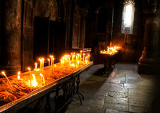 Lighting candles inside Geghard Monastery Stock Images