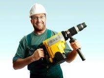 Geglimlachte werkman in de perforator van de helmgreep Stock Afbeeldingen