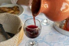 Gegossener Rotwein in einem Glas auf dem Tisch lizenzfreie stockfotografie
