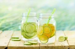Gegoten detox geef, Wijnoogst en pastelkleurtoon, Detox-dieetcitroen en komkommer op houten aardachtergrond water Royalty-vrije Stock Fotografie