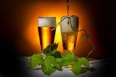 gegoten glazen bier, met hopbladeren op een lichte achtergrond, concept Oktoberfest Stock Foto's