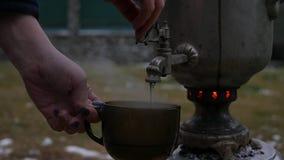 Gegoten thee in een mok in de binnenplaats tijdens het koude seizoen grote oude samovar Langzame Motie stock videobeelden