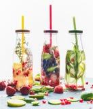 Gegoten water in flessen met drankstro en ingrediënten op witte achtergrond, vooraanzicht royalty-vrije stock afbeelding