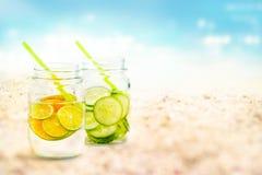 Gegoten watercitroen en komkommer in mok op van het overzeese de zomerdag zandstrand en aardachtergrond Royalty-vrije Stock Afbeelding