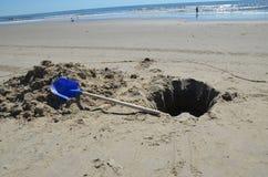 Gegrabenes Loch auf dem Strand mit einer blauen Schaufel Lizenzfreies Stockfoto