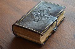 Gegraveerd oud boek met slot op houten lijst Stock Afbeelding