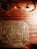 Gegraveerde metaalbloemen op een houten borst Stock Afbeelding