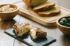 Gegrillte, angefüllte Hühnerbrust mit Brot und Salat stockfotografie