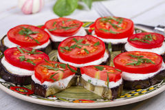Gegrillte Aubergine mit würziger Sauerrahmsoße, -tomaten und -basilikum Stockbilder