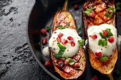 Gegrillte Auberginen mit Jogurtsoße, Granatapfelsamen, Petersilie und Frühlingszwiebel in der Roheisenweinlesewanne stockfoto