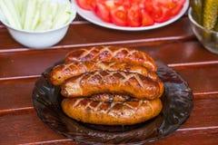 Gegrillte BBQ-Würste und -gemüse stellten auf eine Tabelle ein Stockfotografie
