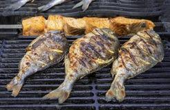 Gegrillte dorada Fische und Scheiben von Lachsen auf dem Grillgitter stockbilder