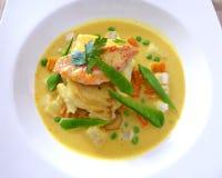 Gegrillte Fische mit der gelben Currysoße lokalisiert auf Weiß stockfotos
