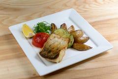 Gegrillte Fische mit Gemüse auf einer Platte des weißen Quadrats Stockbilder