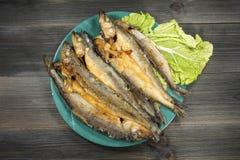 Gegrillte Fische - Schmelz auf einer Platte mit grünem Salat auf einem alten schwarzen hölzernen Hintergrund Stockfotografie