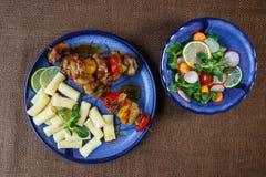Gegrillte Fleischaufsteckspindeln mit Teigwaren auf Platte mit Gemüsesalz Stockfotografie