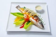 Gegrillte ganze Fische verziert mit den Blättern der Kopfsalat- und Kirschtomate, gedient mit Knoblauchsoße Gebratene ganze Fisch Stockfoto