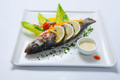 Gegrillte ganze Fische verziert mit den Blättern der Kopfsalat- und Kirschtomate, gedient mit Knoblauchsoße Gebratene ganze Fisch Stockfotografie