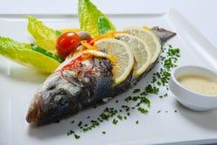 Gegrillte ganze Fische verziert mit den Blättern der Kopfsalat- und Kirschtomate, gedient mit Knoblauchsoße Gebratene ganze Fisch Lizenzfreie Stockfotografie