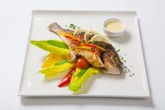 Gegrillte ganze Fische verziert mit den Blättern der Kopfsalat- und Kirschtomate, gedient mit Knoblauchsoße Gebratene ganze Fisch Lizenzfreie Stockfotos