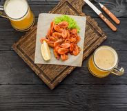 Gegrillte Garnelen auf einem Brett und einem Bierkrug Lizenzfreie Stockfotografie