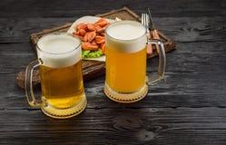 Gegrillte Garnelen auf einem Brett und einem Bierkrug Dunkler Holztisch Stockfoto