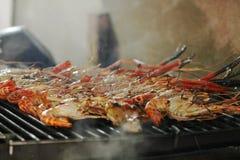 Gegrillte Garnelen auf heißer Holzkohlenplatte mit raucht Fliegen oben Köstliches Meeresfrüchtemenü lizenzfreie stockfotos