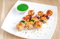 Gegrillte Hühneraufsteckspindeln mit Zucchini- und Kirschtomaten Stockfotografie