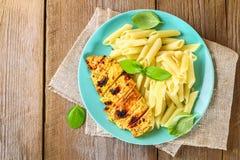 Gegrillte Hühnerbrust und Penne-Teigwaren mit Gewürzen und Basilikum Ein köstliches Abendessen in der rustikalen Art Selektiver F Stockbild