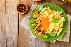 Gegrillte Hühnerbrust und Penne-Teigwaren mit Gewürzen und Basilikum Ein köstliches Abendessen in der rustikalen Art Selektiver F Stockfoto