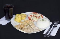 Gegrillte Hühnerleisten, Kartoffeln und Gemüse, dienten mit einem Glas chicha morada (purpurrotes Maisgetränk) lizenzfreies stockbild
