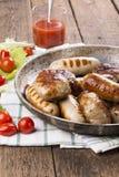 Gegrillte Hühnerwürste und -burger stockfoto