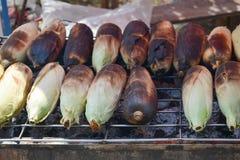 Gegrillte Körner auf der Holzkohle zerreiben am Stall stockbild