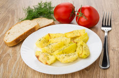Gegrillte Kartoffeln in der Platte, im Brot, im Dill, in den Tomaten und in der Gabel Lizenzfreie Stockbilder