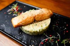 Gegrillte Lachse mit Leberfettleber, -kuskus und -gurke auf weißem Reis stockfotografie