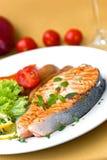 Gegrillte Lachse mit nahem hohem des Kopfsalates und der Tomate Stockbilder